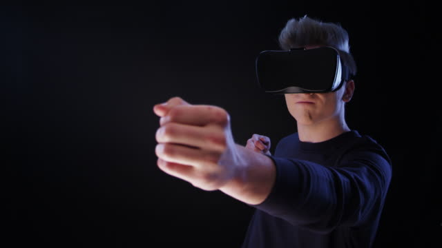 Young man using virtual reality glasses. Aiming with imaginary arch