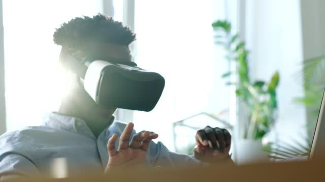 stockvideo's en b-roll-footage met jonge man met behulp van virtual reality bril. denkbeeldige pagina's verplaatsen - menselijke arm