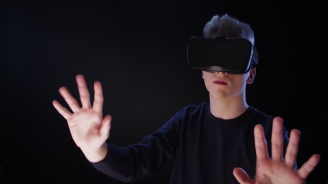 Junger Mann mit virtual-Reality-Brille. Großen imaginäres Objekt berühren