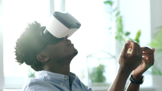 Young man using virtual reality glasses. Touching big imaginary object