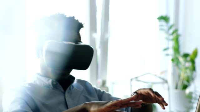 Young man using virtual reality glasses. Touching imaginated device surface