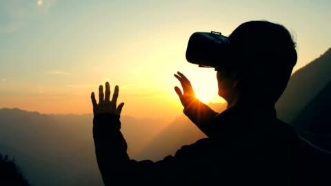 vidéos et rushes de jeune homme à l'aide de micro/casque vr 360 au coucher du soleil - casque