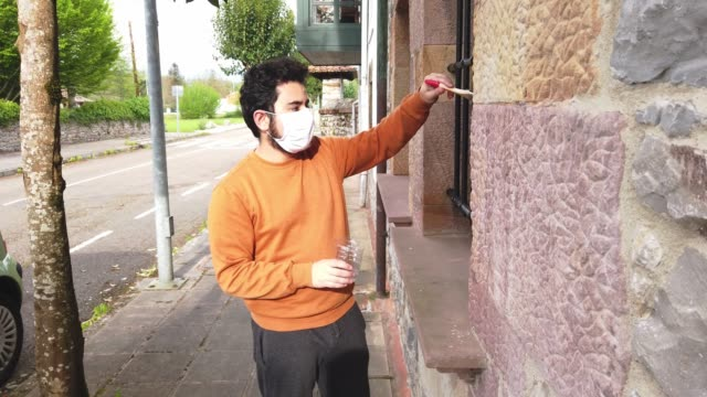 young man varnishing a home window during the covid-19 lockdown - bricolage video stock e b–roll