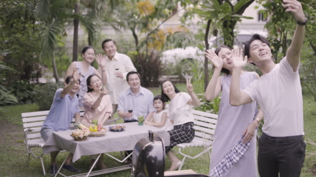 young man video call by smartphone with family in the garden. - vicino di casa video stock e b–roll