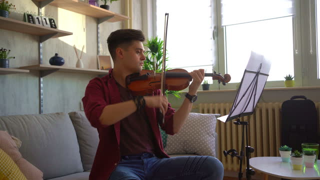 young man violinist practicing violin at living room - violinist stock videos & royalty-free footage