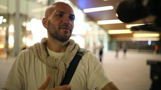 vidéos et rushes de jeune homme vlogging devant le centre commercial la nuit - équipement audiovisuel