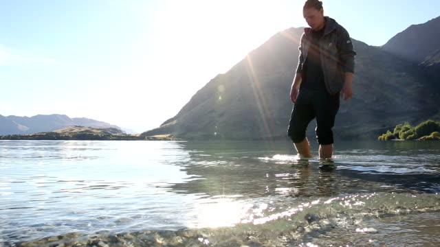 Young man wades along lake edge, contemplative