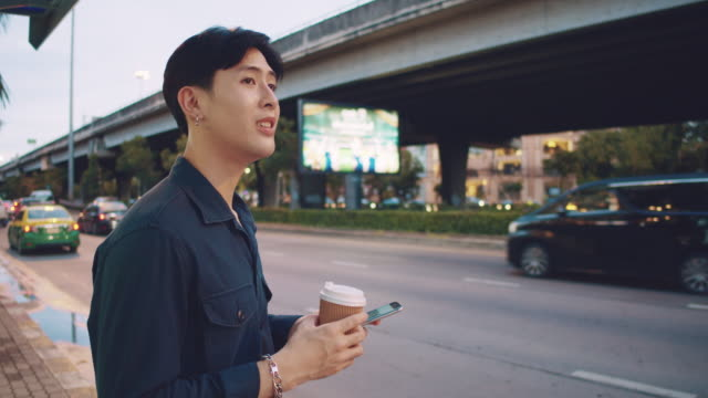 young man waiting for taxi in bangkok city. - roadside stock videos & royalty-free footage