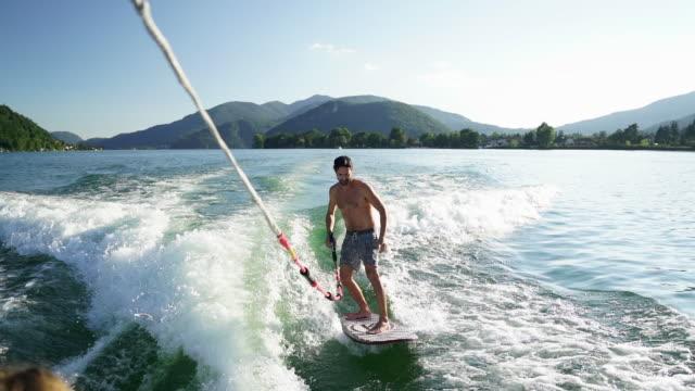 stockvideo's en b-roll-footage met jonge man wake surft op meer bij zonsondergang - kielwater