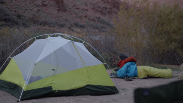Young man wakes up in sleeping bag at Moab campsite and puts on shoes in the morning light.