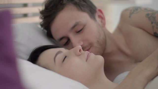 Young man wakes up to 6:30 alarm, leans over to kiss girlfriend's cheek, and gets out of bed
