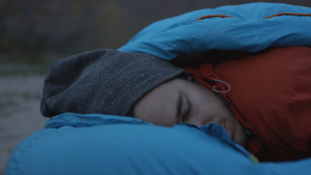 CU. Young man waking up outdoors opens eyes and sits up in sleeping bag.