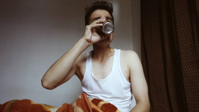 young man waking-up in morning and drinking water. - the morning after stock videos and b-roll footage