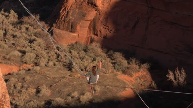 young man walking a slackline over a canyon near moab, utah - corda video stock e b–roll