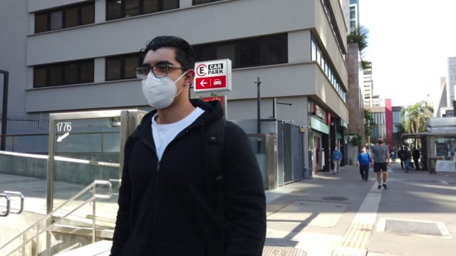 young man walking at paulista avenue, sao paulo. wearing protective face mask. - walkable city stock videos & royalty-free footage