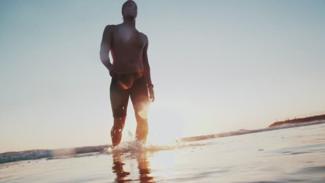 sm young man walking back after swimming at sunset - torso stock videos & royalty-free footage