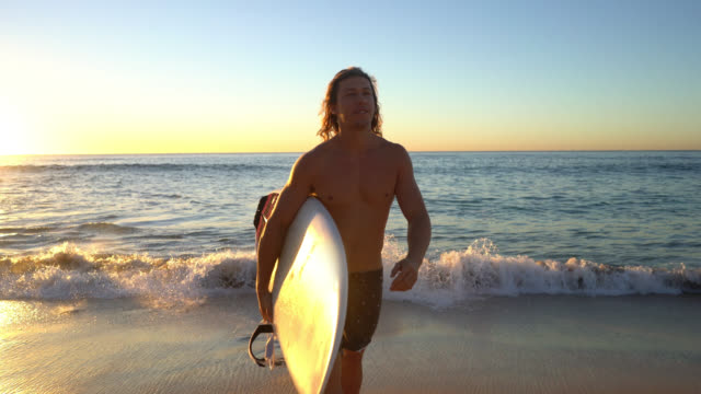 young man walking back to the beach after surfing smiling - surfing stock videos & royalty-free footage