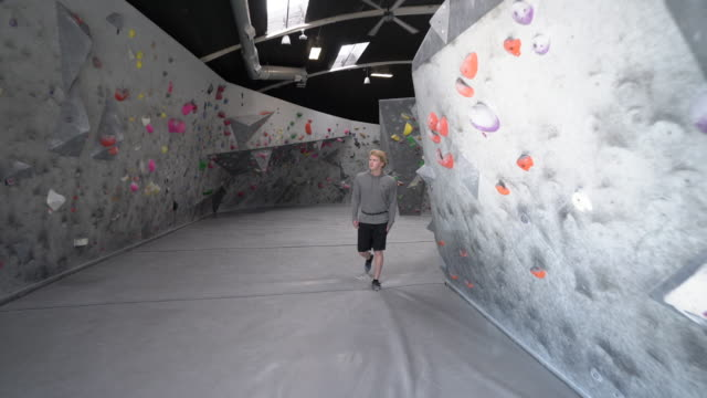 ws ts young man walking by a rock climbing wall - climbing wall stock videos & royalty-free footage