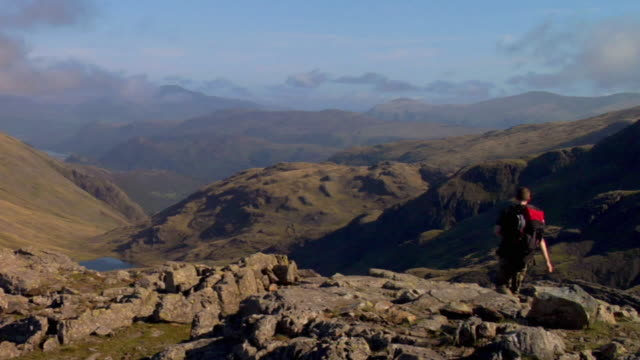 ws young man walking down mountain / lake district, cumbria, uk - physical geography stock videos & royalty-free footage