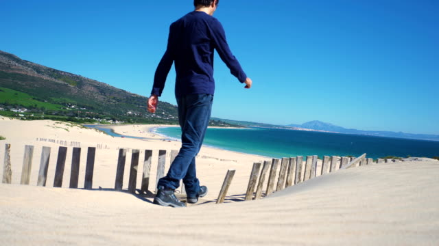 a young man walking in a dune sand with ocean and africa coast behind him - only mid adult men stock videos & royalty-free footage