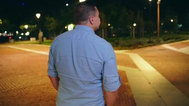 Young man walking in city park at night and relaxing