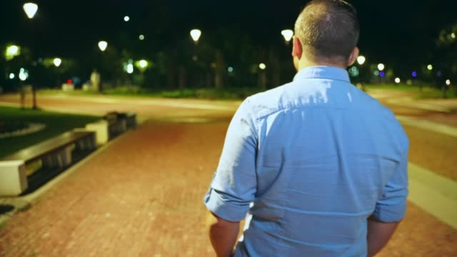Young man walking in city park at night looking around
