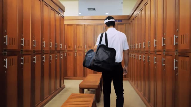 young man walking in the locker room at the gym.sports cinemagraphs - golfer stock videos & royalty-free footage