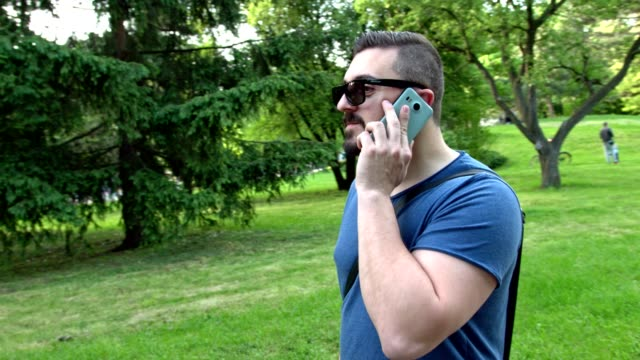 Young man walking in the park and discussing something on the phone