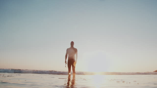 ws young man walking into the sea at sunset - torso stock videos & royalty-free footage
