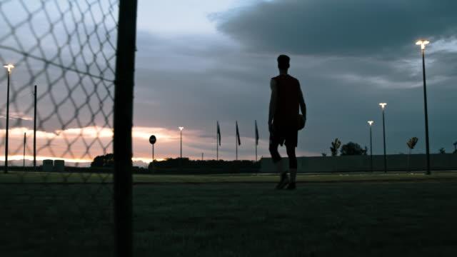 vidéos et rushes de ms jeune homme marchant outre du terrain extérieur de basket-ball au crépuscule - joueur de basket ball