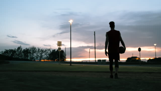 ms young man walking off outdoor basketball court at dusk - tracking shot stock videos & royalty-free footage