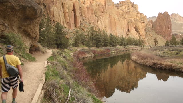 a young man walking on a dirt trail inside of smith rock state park. - smith rock state park stock videos & royalty-free footage