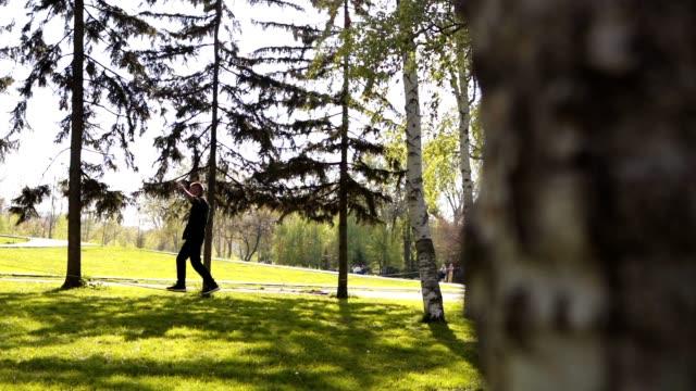 stockvideo's en b-roll-footage met jonge man lopen op een slackline in een park - sunny