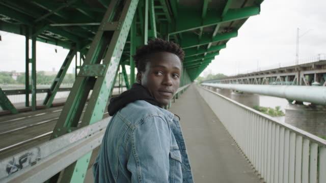 vidéos et rushes de jeune homme qui marche sur roadtruck sous le pont. solitude - mode de vie alternatif