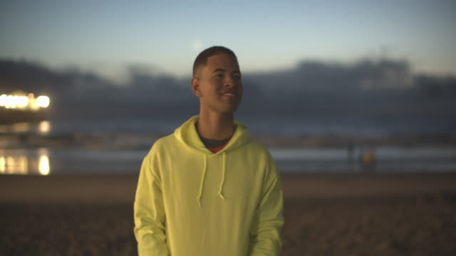 young man walking on the beach at night - sweatshirt stock videos & royalty-free footage