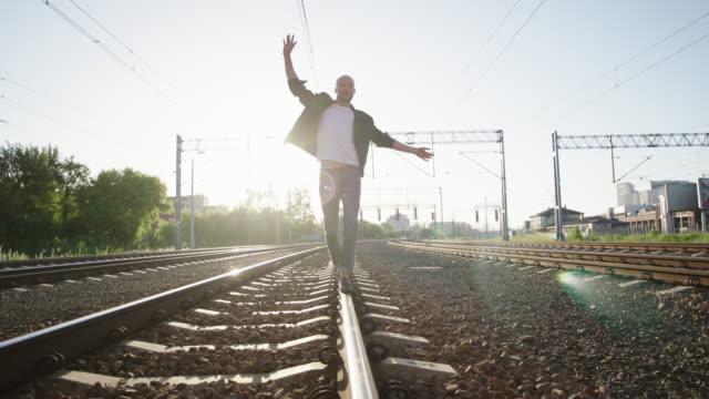 vídeos de stock e filmes b-roll de young man walking on the railway. rock and roll style. - equilíbrio