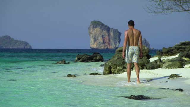 ws young man walking on tropical beach, krabi, thailand - see other clips from this shoot 1459 stock videos and b-roll footage