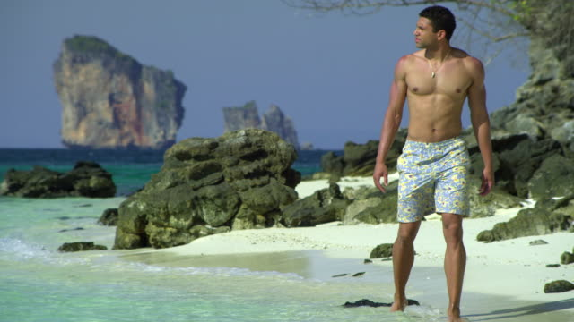 ws ms young man walking on tropical beach, krabi, thailand - see other clips from this shoot 1459 stock videos and b-roll footage
