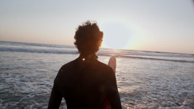 vídeos de stock e filmes b-roll de sm young man walking out to the sea at sunset - rebentação