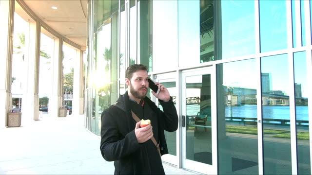 vídeos de stock, filmes e b-roll de jovem caminhando do lado de fora comendo maçã, telefone móvel - bolsa tiracolo bolsa