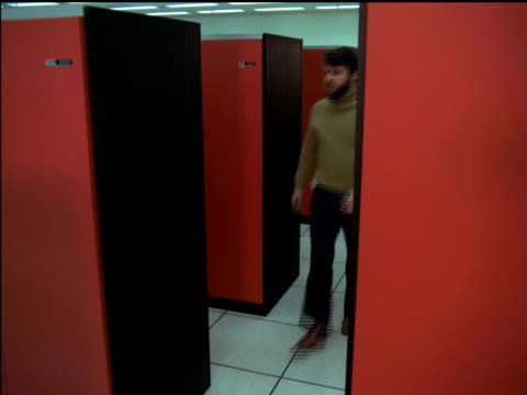 / young man walking through computer server room / young woman walking out of computer server room. 1970s computer server room on january 01, 1971 - computer network stock videos & royalty-free footage
