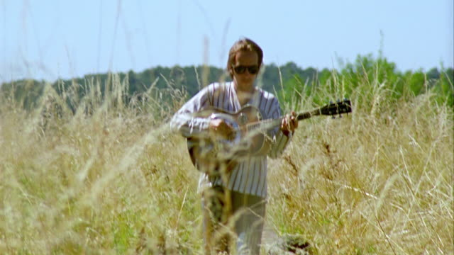 MS, CU, Young man walking through grass in meadow and playing guitar, Saint Ferme, Gironde, France