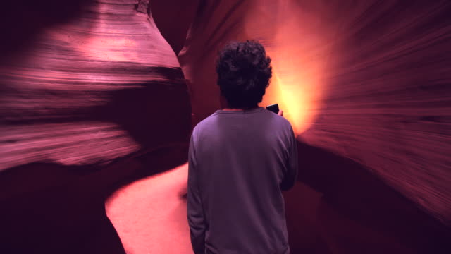 vídeos de stock, filmes e b-roll de ws young man walking through the rock formations of antelope canyon - estupefação