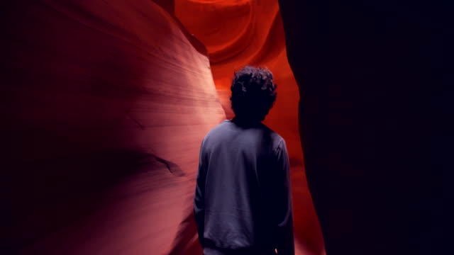 ws young man walking through the rock formations of antelope canyon - canyon stock videos & royalty-free footage