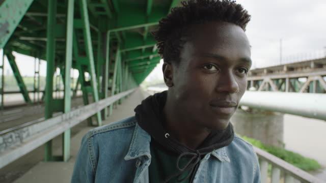 vidéos et rushes de jeune homme marchant sous le pont. solitude - tête composition