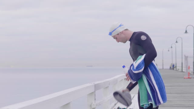 vídeos de stock, filmes e b-roll de young man walking up the pier stopping to appreciate the view - touca de natação