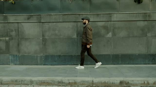 vídeos de stock, filmes e b-roll de jovem caminhando - parede