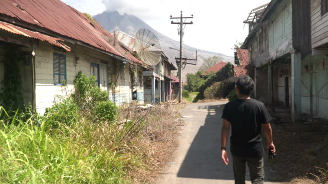 young man walking with feeling of fear in abandoned ghost berastepu town near mt.sinabung - indonesia stock videos & royalty-free footage