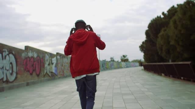 young man walking with headphones - 20 24 years stock videos & royalty-free footage