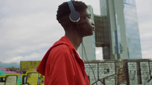 young man walking with headphones - listening stock videos & royalty-free footage